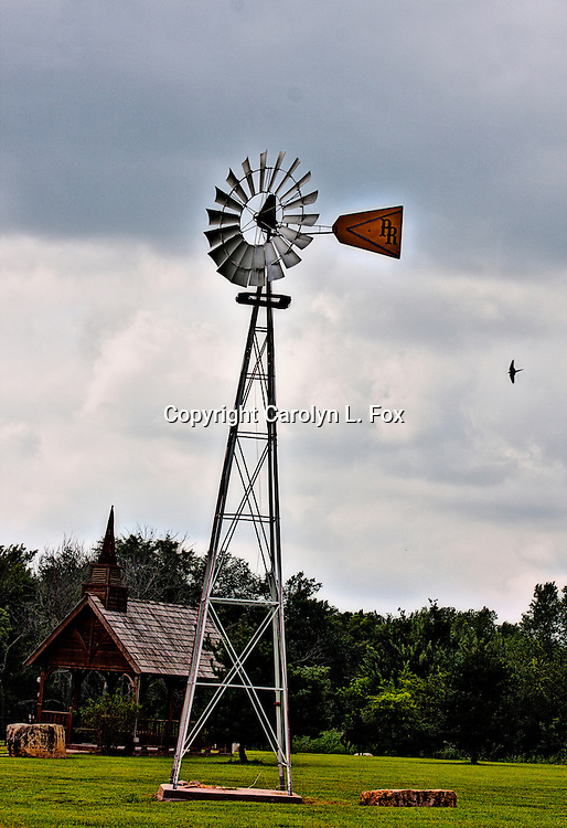An old windmill stands in a field in Kansas.