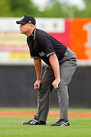 Umpire Carlos Torres handles the calls on the bases during the South Atlantic League game between the Greensboro Grasshoppers and the Hickory Crawdads at L.P. Frans Stadium on May 18, 2011 in Hickory, North Carolina.   Photo by Brian Westerholt / Four Seam Images