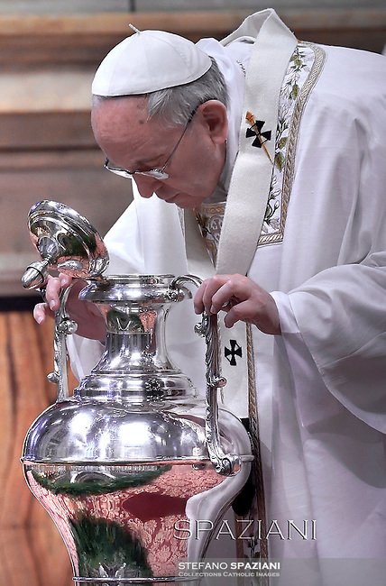 Pope Francis blows in an amphora containing holy oil during a Chrism mass, Maundy Thursday.at St Peter's basilica in Vatican.April 2, 2015