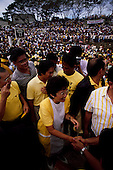 """Manila, Philippines<br /> February 1986<br /> <br /> Corazon Aquino campaigning for President of the Philippines in 1986.<br /> <br /> Corazon Aquino was born into one of the wealthiest families in the Philippines, Mrs. Aquino began her political education by playing the dutiful wife as the political career of her husband, Benigno Aquino Jr., expanded. In less than 20 years he emerged as one of the chief potential rivals of Mr. Marcos, who was then president. When Mr. Marcos declared martial law in 1972, her husband was arrested and imprisoned for seven years. He was assassinated in 1983 after returning to the Philippines from a three-year exile in the United States. Mr. Marcos was widely blamed for the murder. It was at Mr. Aquino's funeral that Mrs. Aquino, became a national symbol, demonstrating the dignity and composure that would characterize her most difficult moments as president. <br /> <br /> Mrs. Aquino came to power through what amounted to popular acclaim -- what the Philippino people called """"people power"""" -- expressed by huge crowds that gathered in support of her. Her popularity reached its peak during her presidential campaign against Mr. Marcos in January 1986, when she was surrounded by enthusiastic crowds chanting, """"Cory! Cory! Cory!'""""<br /> <br /> Her act of knocking down a dictator and bringing democracy to the Philippines was a high point in the country's modern history, and it offered a model for nonviolent uprisings that has been repeated often in other countries...Mrs. Aquino, was often criticized as an indecisive and ineffectual leader. But she combined passivity and stubbornness and an unexpected shrewdness to hold firm against powerful opponents from both the right and the left, and one of her greatest accomplishments as president was fending off a half dozen coup attempts. <br /> <br /> The restoration of democracy, and the transition to a new president, were Mrs. Aquino's prime legacies. Yet she led demonstrations against all 3 of her su"""