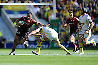 Mako Vunipola of Saracens looks to hand off Nathan Hines of ASM Clermont Auvergne during the Heineken Cup semi-final match between Saracens and ASM Clermont Auvergne at Twickenham Stadium on Saturday 26th April 2014 (Photo by Rob Munro)