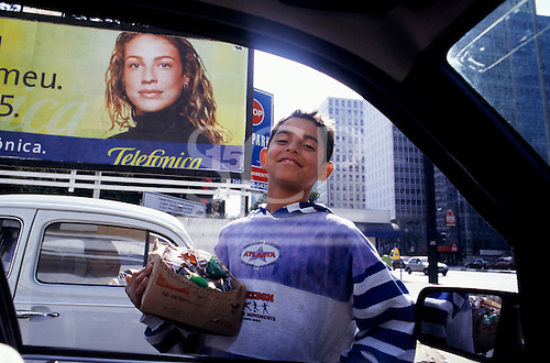 Sao Paulo, Brazil. Boy selling sweets on the street, big telephone advertisment in the background.