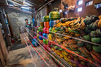 Nilar, Plastic Rope Factory, Taungoo, Myanmar, 2016<br /> Daw Khin Nilar Htun makes plastic rope in Taungoo Myanmar. She used to work in a factory that used a machine to make twine. She designed a modification that allowed the machine  to make a thicker rope, and her husband and cousin welded the remodeled machine together. She makes about 70 bunches a day, each bunch with ten ropes. Her husband helps by selling rope and clay pots in the market, making about $2 to $5 a day. Nilar works about 7.5 hours a day but has to hire some help as she also cooks, cleans, and takes care of their five children, ages 4–24. She received a loan of $500 from BRAC and was able to open a small restaurant. She and her husband make about $55 a day. Their goal is to educate their children. One of their daughters is now an engineer, and another is a nurse.