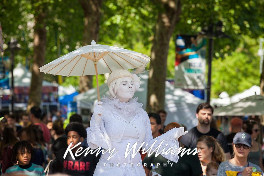 Woman with umbrella and white dress street performing, Northwest Folklife Festival 2016, Seattle Center, Washington, USA.