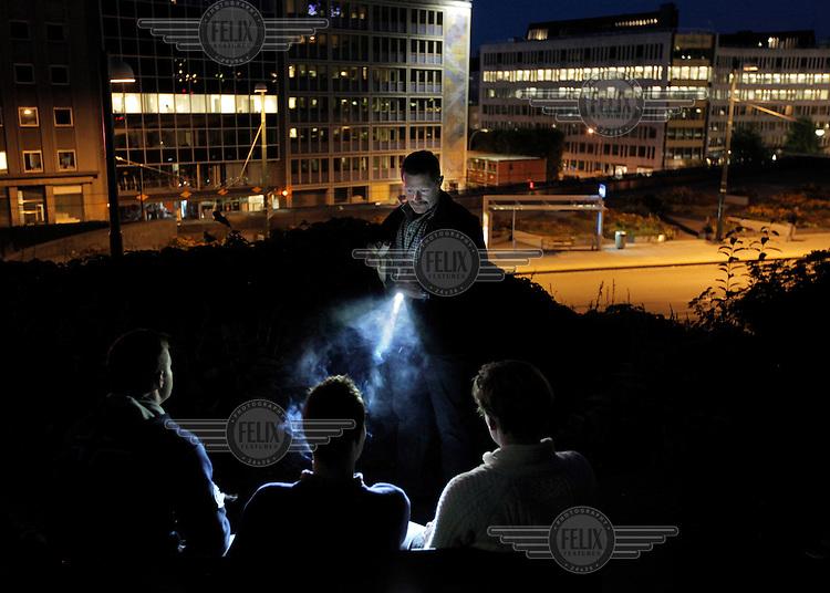 Stig Gaustad , bevæpnet med en banan, sjekker ungdomer som røyker dop i Slottsparken.  Sentrum Politistasjons etteretningsavdeling følger med på utelivet i Oslo sentrum. . (Foto:Fredrik Naumann/Felix Features)
