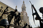 Port-au-Prince, Haiti<br /> November 1987<br /> <br /> Soldiers leaving the city Cathedral after quailing a violent scene prior to elections to be held on November 29th, the first attempt at a democratic election in Haiti. It was unsuccessful as 34 people were killed at a polling station and elections were moved up to February 1988.<br /> <br /> Leslie François Manigat won the election with many political parties boycotting. He had military backing but once in office he sought greater control over the military in an effort, to fight corruption. Manigat's government was overthrown by General Henri Namphy within months.