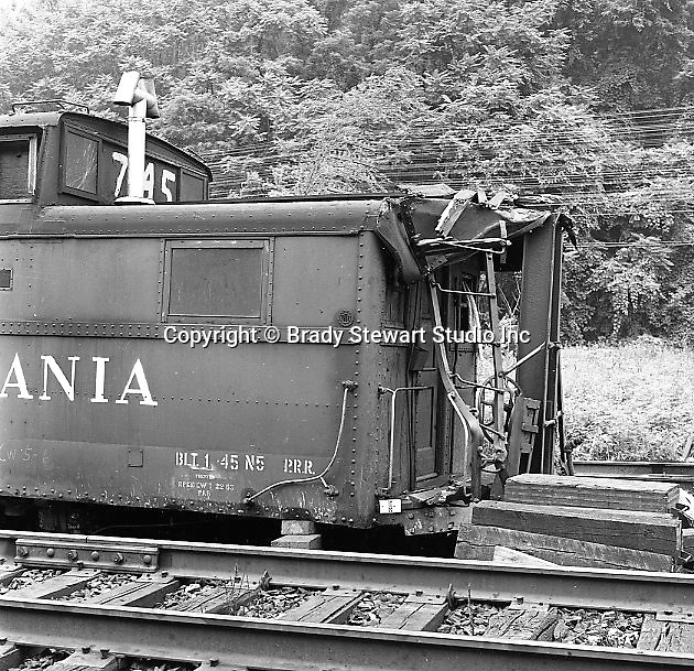 Corliss PA - View of a damaged caboose at an accident site near the train station at Corliss Pennsylvania.  The assignment was for the PA Railroad due to a train derailment near the station.  Brady Stewart Studio was a contract photography studio for the railroad from 1955 through 1965.