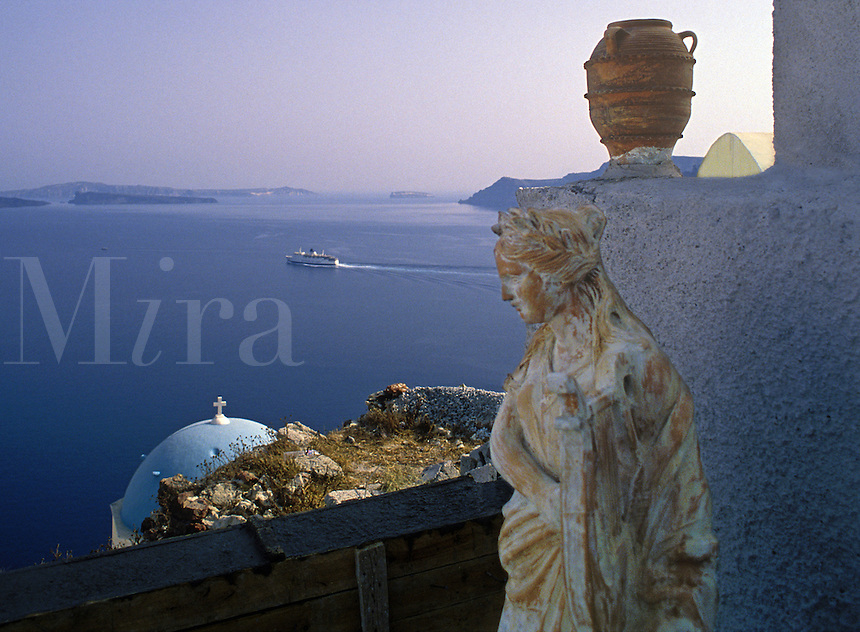 Modern-day clay statue, pottery, and old church dome stand watch as an inter-island ferry leaves Santorini, Greece.