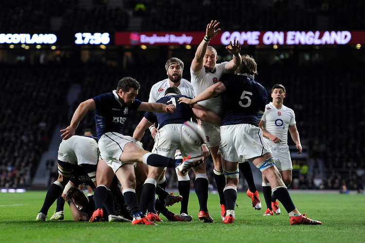 Greig Laidlaw of Scotland sends up a box kick as Mike Brown of England attempts to block