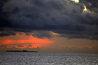 Sun setting over an island in a sky filled with heavy storm clouds, Maldives.