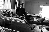 Africa, Sudan, Magwi County, Nimule, Southern Sudan - The woman pictured here resting at Merlin Hospital was shot by the Lord's Resistance Army during an ambush in the village of Mugale, about seven kilometers away, just a few days before. One other man was shot and killed. Since the attack the 15,000 inhabitants of Mugale have been making an exodus out of the village toward nearby Nimule. The war in the region began in 1986 between the Lord's Resistance Army and the Ugandan People's Defense Forces (UPDF). The LRA has reigned terror and carnage on Northern Uganda and Southern Sudan ever since. The ongoing conflict has significantly damaged the region and has left an ongoing burden on the local population. December 2005 © Stephen Blake Farrington