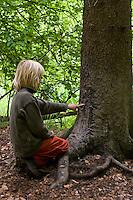Kind an einem Schubberbaum, Kratzbaum, Malbaum, Wildschwein hat durch Reiben die Rinde im unteren Bereich eines Baumes abgewetzt, Schwarzwild, Sus scrofa, wild boar, pig