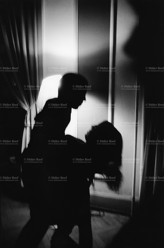 Switzerland. Canton Ticino. Locarno. Party at the Grand Hotel for the last night of Locarno Festival. A man dances with a woman passionately in the dim light. Shadows and darkness. A couple is enjoying a sexy move. The Locarno Festival (formerly called the Festival del film Locarno and commonly referred to as the Locarno Film Festival) is an annual film festival held every August © 2005 Didier Ruef