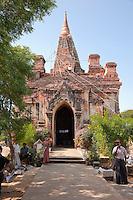 Myanmar, Burma.  Manuha Temple, Bagan, 11th. Century.  Repair Work in Progress.  Souvenir Vendors in Front.