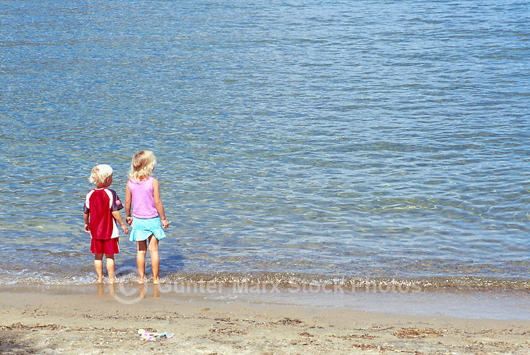 Two Children standing on a Sandy Beach along a West Coast Seashore (No Model Release Available)