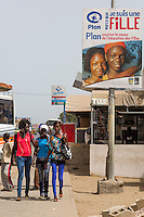 Senegal, Saint Louis.  Young Senegalese Women in European Clothes and Sign Promoting Education for Women.