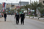 Iraqis walk past shops that are shuttered to help prevent the spread of the coronavirus, in Baghdad, Iraq, on March 21, 2020. Iraq announced a weeklong curfew to help fight the COVID-19 pandemic. Photo by Hassani Al-Asadi
