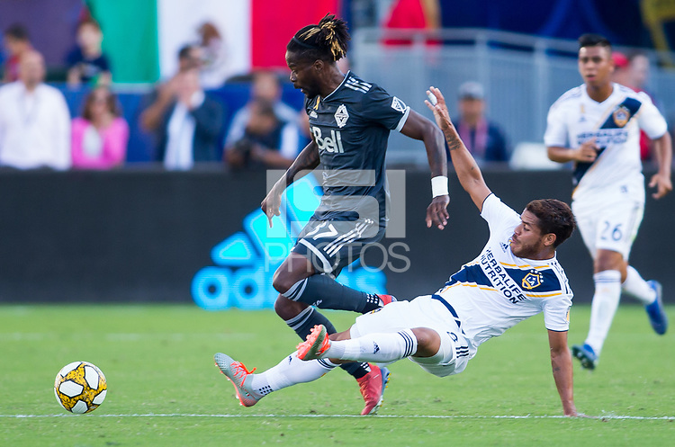 CARSON, CA - SEPTEMBER 29: Jonathan dos Santos #8 of the Los Angeles Galaxy slides Tosaint Ricketts #87 of the Vancouver Whitecaps during a game between Vancouver Whitecaps and Los Angeles Galaxy at Dignity Health Sports Park on September 29, 2019 in Carson, California.