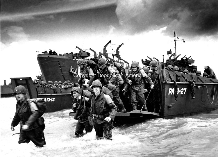 American reinforcements, arrive on the beaches of Normandy from a Coast Guard landing barge into the surf on the French coast on June 23, 1944 during World War II. They will reinforce fighting units that secured the Norman beachhead and spread north toward Cherbourg.  (AP Photo/U.S. COAST GUARD)