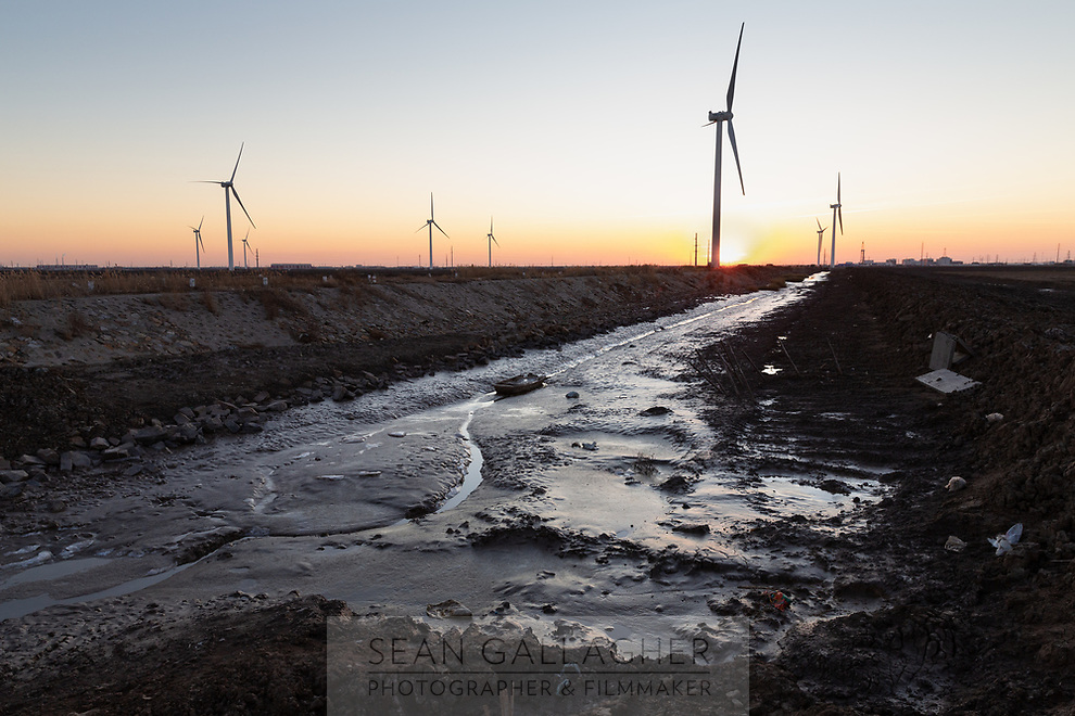 A windfarm near the Bahai Bay coast. This stretch of coastline has been identified as one of the most vulnerable in China and will be one of the first to feel climate change impacts including rising sea levels and increased storm surges. China, 2019.