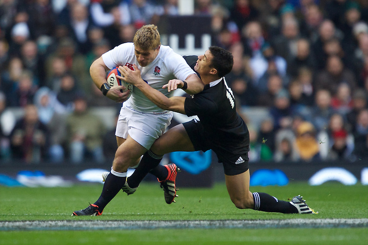 Tom Youngs of England is tackled by Dan Carter of New Zealand during the QBE Autumn International match between England and New Zealand at Twickenham on Saturday 01 December 2012 (Photo by Rob Munro)