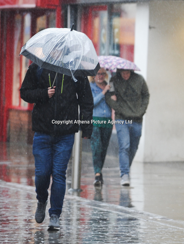 Shoppers in Swansea city centre brave the weather as heavy rain hits South Wales on Sunday.