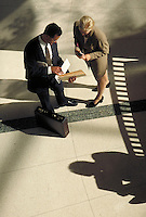 Man and woman discussing business; looking over documents. High view. Professionals. Lawyers.Businesswoman. Businessman. Denver Colorado USA.