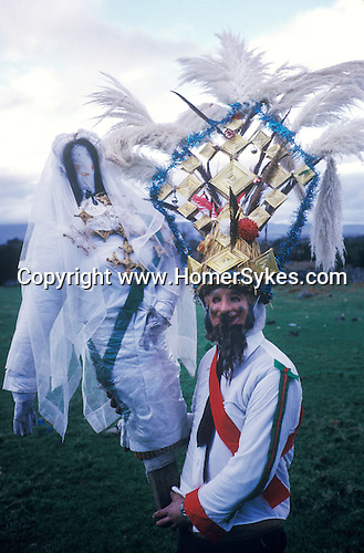 Biddy Boys 1970s. Killorglin Co Kerry Ireland. February 2nd festival to celebrate the Celtic Saint Brigid. A doll - St Bridgid - is taken from house to house,  paraded through the street by Biddy Boys.
