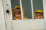 children looking at rain through window