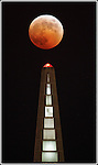 A full eclipse of the moon, like an evil pumpkin, tops San Francisco Transamerica Pyramid. ..