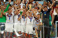 Philipp Lahm of Germany celebrates winning the FIFA World Cup by lifting the trophy with his team mates and Germany manager Joachim Low