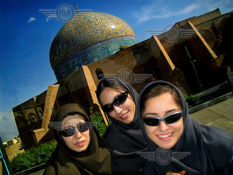 Three women in Chadors and sunglasses smile for a picture near the Sheikh Lotf Allah Mosque.