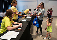 Alexis Turnbull, right, along with her son Granger Turnbull, 1, and daughter Hadley Turnbull, 3, picks up her race packet from Brienne Austin far left and Theresa Cook Friday Oct. 8, 2021, for the 2021 Run Bentonville Half Marathon. Runners where picking up there packets at the Run Expo that was being held at Thaden Airport. The race starts at 7pm on the downtown Bentonville Square. Go to nwaonline.com/211008Daily/ to see more photos from around Northwest Arkansas. (NWA Democrat-Gazette/Spencer Tirey)