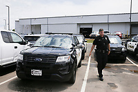 Springdale Police Officer Nick Stone exits a police vehicle, Friday, July 16, 2021 at the Springdale Police Station in Springdale. The supply chain that has limited the amount of new cars for sale will hit the police departments as they try to replace patrol cars. Officials say they must make do with what they have. Check out nwaonline.com/210717Daily/ for today's photo gallery. <br /> (NWA Democrat-Gazette/Charlie Kaijo)