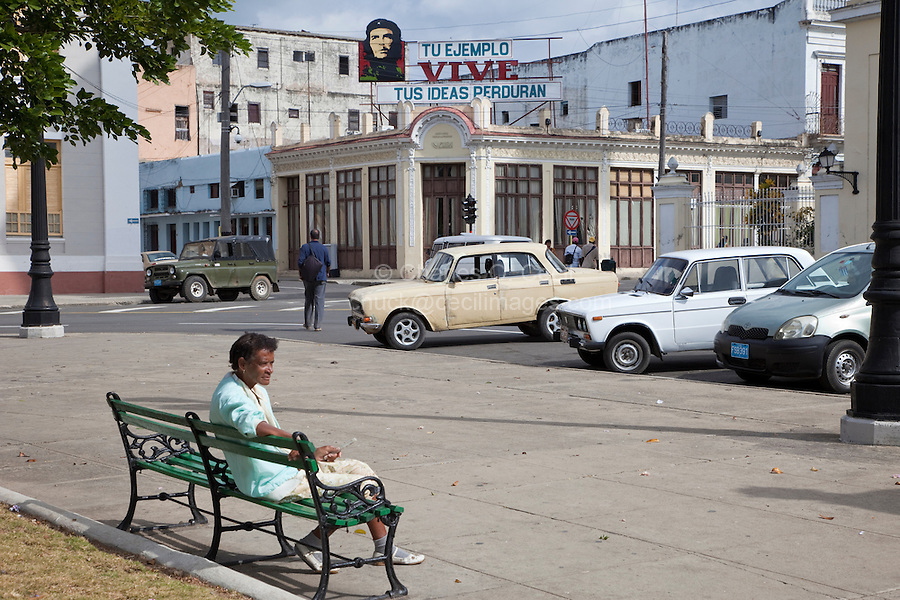"""Cuba, Cienfuegos.   Street Scene adjacent to Parque Marti.  Billboard to Che Guevara.  """"Your example lives; your ideas will endure."""""""