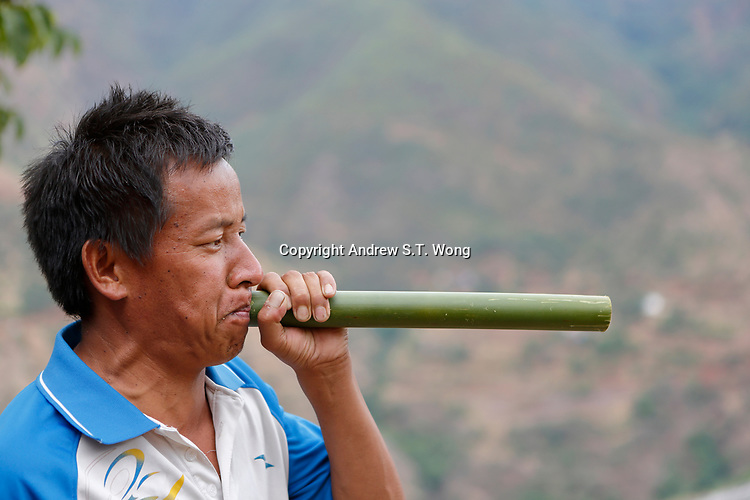 Wumu Village, Yulong County, Yunnan Province, China - Dongba priest He Jixian of the Naxi ethnic group performs during a rain ceremony to invoke rain amidst current inclement weather, June 2019