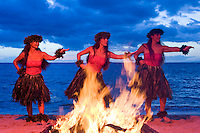 Three hula dancers perform a dance for Pele next to a fire on the beach at Makena, Maui.