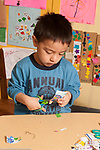 Educaton preschool  3-4 year olds fine motor activity cutting paper with scissors vertical