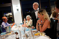 Jean Marchi, maître d'hôtel of restaurant 'Le Calypso', serves portions of bouillabaisse to diners in the dining room, Le Calypso, Marseille, France, 25 August 2012