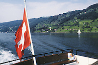 Switzerland. Zoug. A young girl is riding a public boat on the lake of Zoug.  A swiss flag floats in the air.  A sailboat is also enjoying the beautiful summer day.© 1989 Didier Ruef