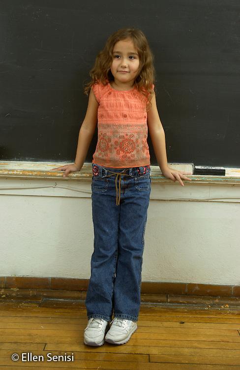 MR / Schenectady, NY.Yates Arts in Education Magnet School, Grade 2.Arts-Themed Urban Elementary School.Full length portrait of girl (7) standing at blackboard..MR: Dun4.© Ellen B. Senisi