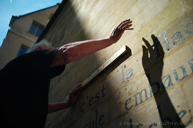 """Jan Willem prepares the wall to paint, """"Le Bateau Ivre,"""" a poem by Arthur Rimbaud on the wall of the Public Treasury at place Saint Sulpice in Paris, France on May 30, 2012."""