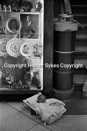 African American child in carry cot placed on floor below souvenirs of Martin Luther King and the Kennedy's in a Greyhound Bus station. Atlanta, Georgia 1969,