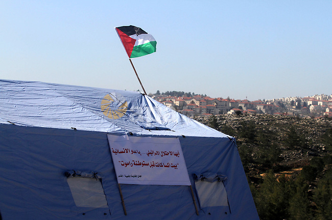 A Palestinian flag flies on a tent in the village of Beit Iksa in West Bank, between Ramallah and Jerusalem, Saturday, Jan 19, 2013. Palestinian activists have set up a protest camp in Beit Iksa to demonstrate against what they say is an Israeli land grab. The Palestinians seem to be adopting a tactic used by Jewish settlers, who establish communities hoping the territory will remain theirs once structures are built. Photo by Issam Rimawi
