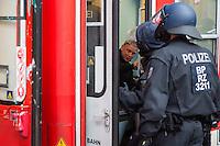 """Proteste gegen Naziaufmarsch """"Tag der Patrioten"""".<br /> Mehere zehntausend Menschen protestirten am Samstag den 12. September 2015 in Hamburg gegen einen von Nazis und Hooligans geplanten Aufmarsch unter dem Motto """"Tag der Patrioten"""". Der Aufmarsch war im Vorfeld gerichtlich untersagt worden, da davon auszugehen sei, dass von ihm Gewalttaten gegen Personen ausgehen wuerden. Die Nazis wichen am Samstag daraufhin nach Bremen aus, wo der Aufmarsch jedoch auch untersagt wurde.<br /> Trotz Verbot versammelten sich an verschiedenen Orten in Hamburg mehrere zehntausend Menschen und protestierten gegen Rassismus und fuer ein Bleiberecht fuer gefluechtete Menschen.<br /> Vor dem Hauptbahnhof kam es zu kleineren Auseinandersetzungen mit der Polizei, die mit 8 Wasserwerfern, Polizeihubschrauber und Beamten aus Bayern, Schleswig-Holstein, Baden-Wuertemberg und Hamburg im Einsatz war.<br /> Als eine Gruppe von ca. 10 bis 15 Nazis und Hooligans im Hauptbahnhof Menschen angriffen, drohte die Lage kurzzeitig zu eskalieren. Die Angreifer mussten aber vor Gegendemonstranten in einen Zug fluechten, wo sie von der Polizei festgesetzt wurden. Der Verkehr durch den Hauptbahnhof war ueber lange Zeit eingestellt, da die Polizei weitere Nazis und Hooligans in ankommenden Zuegen befuerchtete und Auseinandersetzungen verhindern wollte.<br /> Im Bild: Rechte, die in den Zug gefluechtet sind.<br /> 12.9.2015, Hamburg<br /> Copyright: Christian-Ditsch.de<br /> [Inhaltsveraendernde Manipulation des Fotos nur nach ausdruecklicher Genehmigung des Fotografen. Vereinbarungen ueber Abtretung von Persoenlichkeitsrechten/Model Release der abgebildeten Person/Personen liegen nicht vor. NO MODEL RELEASE! Nur fuer Redaktionelle Zwecke. Don't publish without copyright Christian-Ditsch.de, Veroeffentlichung nur mit Fotografennennung, sowie gegen Honorar, MwSt. und Beleg. Konto: I N G - D i B a, IBAN DE58500105175400192269, BIC INGDDEFFXXX, Kontakt: post@christian-ditsch.de<br /> Bei der Bearbeitung der Datei"""