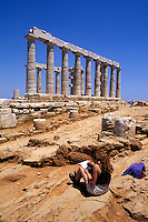 Artist drawing the wonderful ruins of Temple of Poseidon in Greece