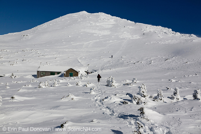 A winter hiker traveling north on the Gulfside Trail (Appalachian Trail) near Madison Spring Hut in the New Hampshire White Mountains during the winter months. Mount Madison, the northernmost peak in the Presidential Range, is in the background. Originally built in 1888, this is how Madison Spring Hut looked in 2010 before it was renovated in the fall and spring months of 2010-2011.