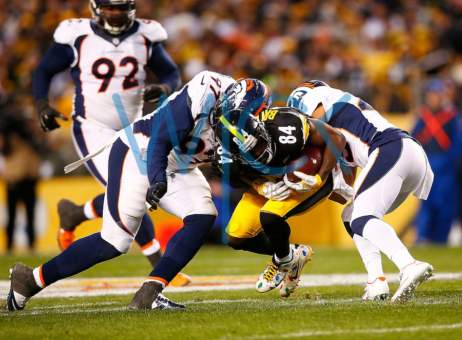 Antonio Brown #84 of the Pittsburgh Steelers is tackled by Malik Jackson #97 of the Denver Broncos after catching a pass in the first half during the game at Heinz Field on December 20, 2015 in Pittsburgh, Pennsylvania. (Photo by Jared Wickerham/DKPittsburghSports)