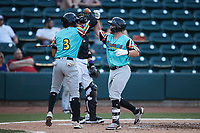 Blaine Crim (9) of the Llamas de Hickory bashes forearms with teammate Jonathan Ornelas (3) after hitting a home run against the Winston-Salem Rayados at Truist Stadium on July 6, 2021 in Winston-Salem, North Carolina. (Brian Westerholt/Four Seam Images)