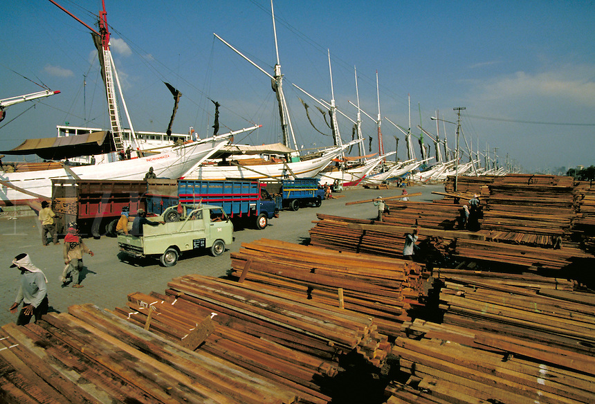 A shipyard located in Jakarta, Indonesia with lumber stacks ready for shipment to other islands in the Indonesia chain of islands; boats, lumber, ships, construction materials, commerce, trade. shipyard in Jakarta, Indonesia. Jakarata, Indonesia shipyard.